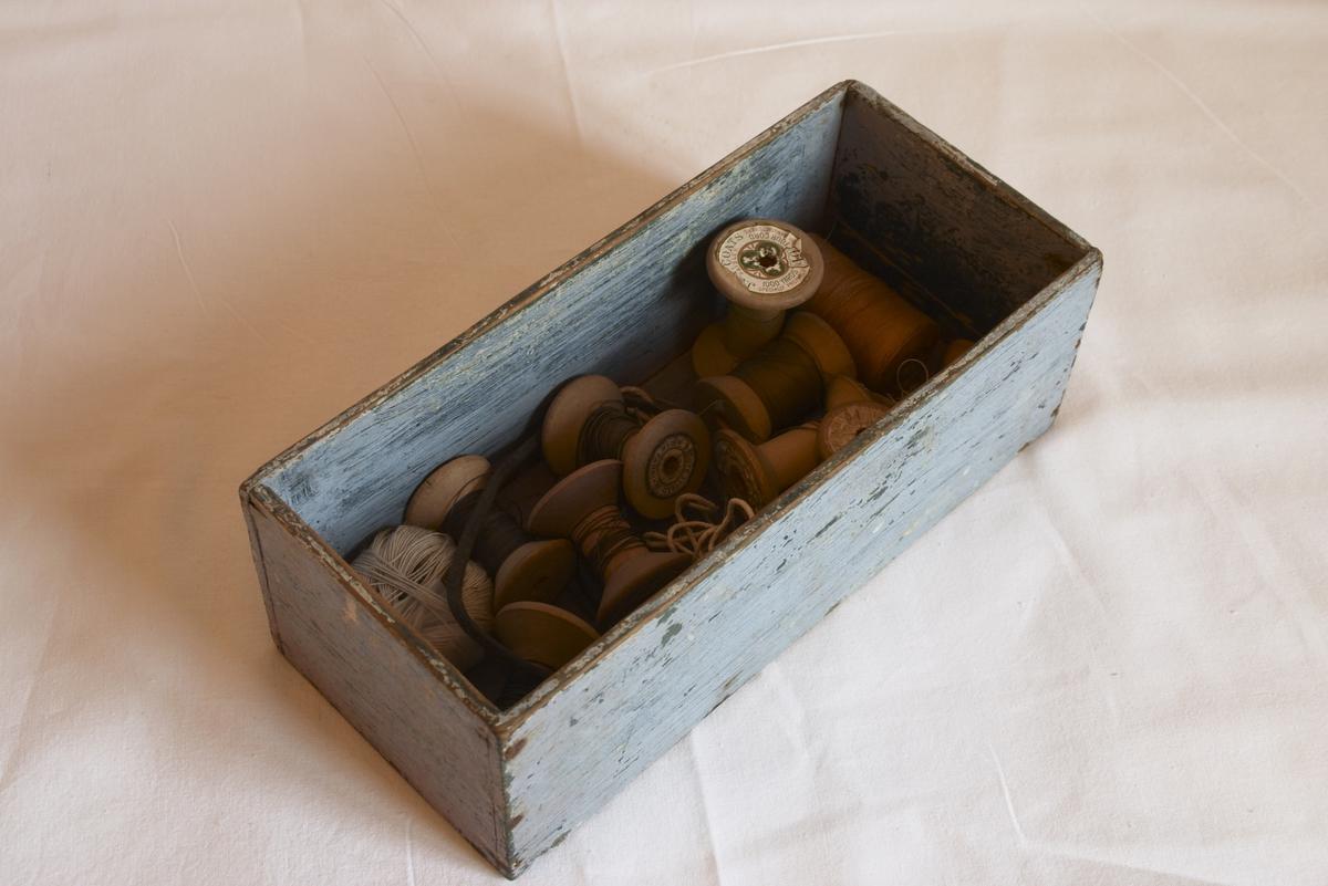 Laget av tre og malt i en lyseblå farge. I skuffen finnes diverse trådsneller og tråd.