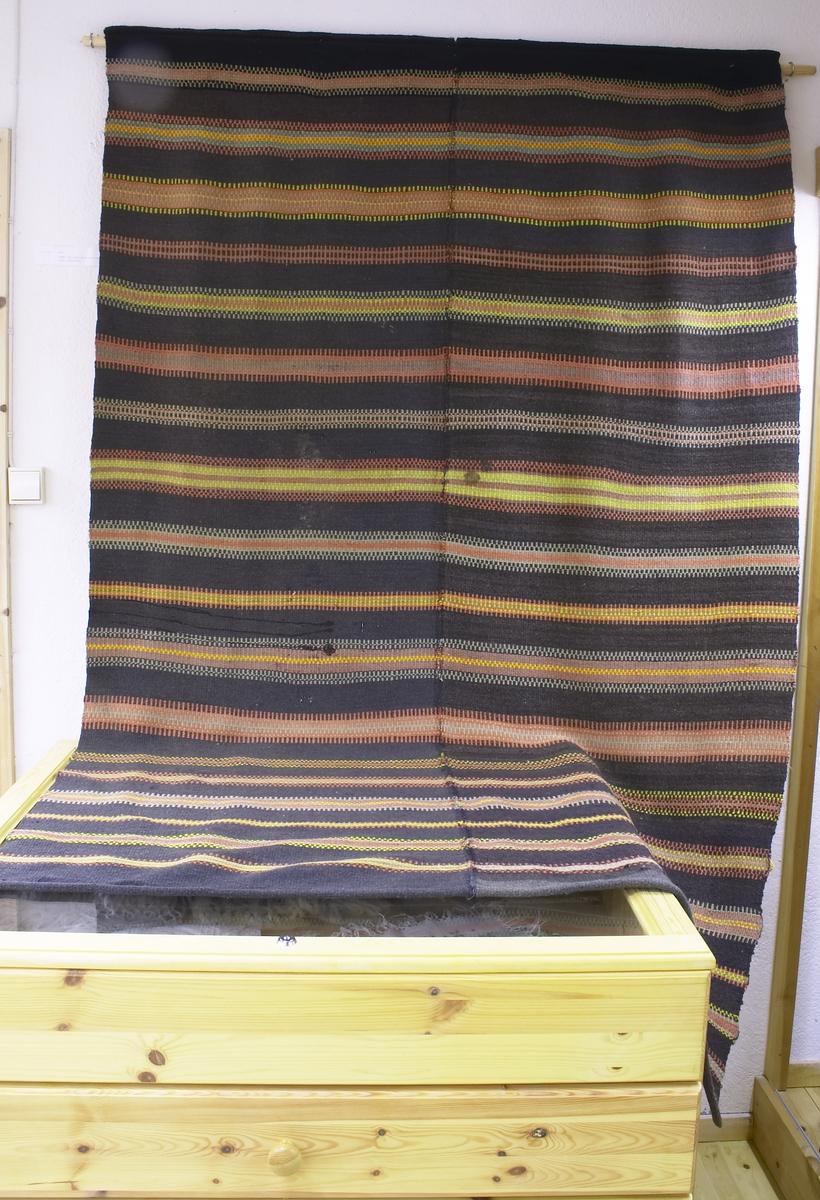 Vevd i to vever som så er sydd sammen på midten til et stort teppe. Vevd av garn som har sort bunnfarge med striper i rød, gul og grønn farge.