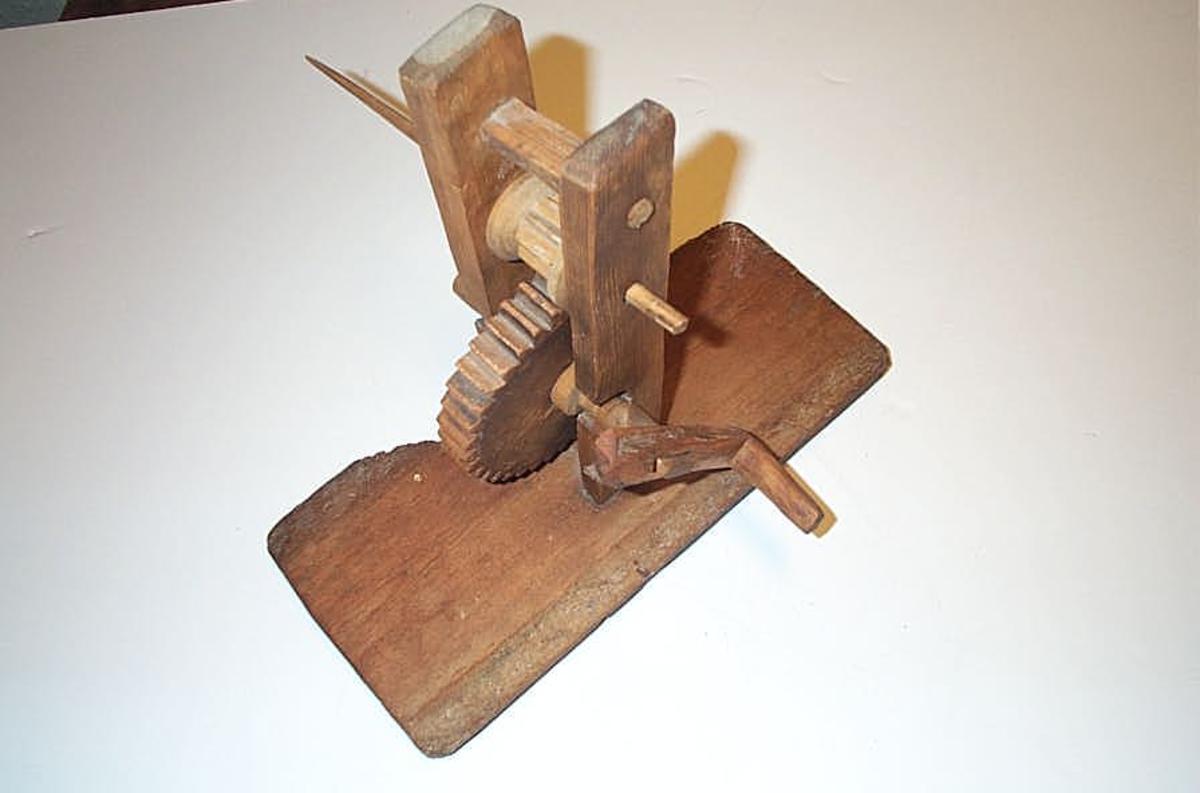 1 spjoletre.  Paa et bundbret (defekt) 17 x 35,5 cm staar to 26,3 cm høie opstandere. I disse er anbragt to spikkete drevhjul av 14 cm diameter og 3,5 diameter. Gjennem det øverste lille drev gaar spjoletangen og dreies dette rundt ved ei sveiv der er fastsat til nederste drevs (tandhjuls) aksel. Kjøpt av Sjur Aafet, Feios.