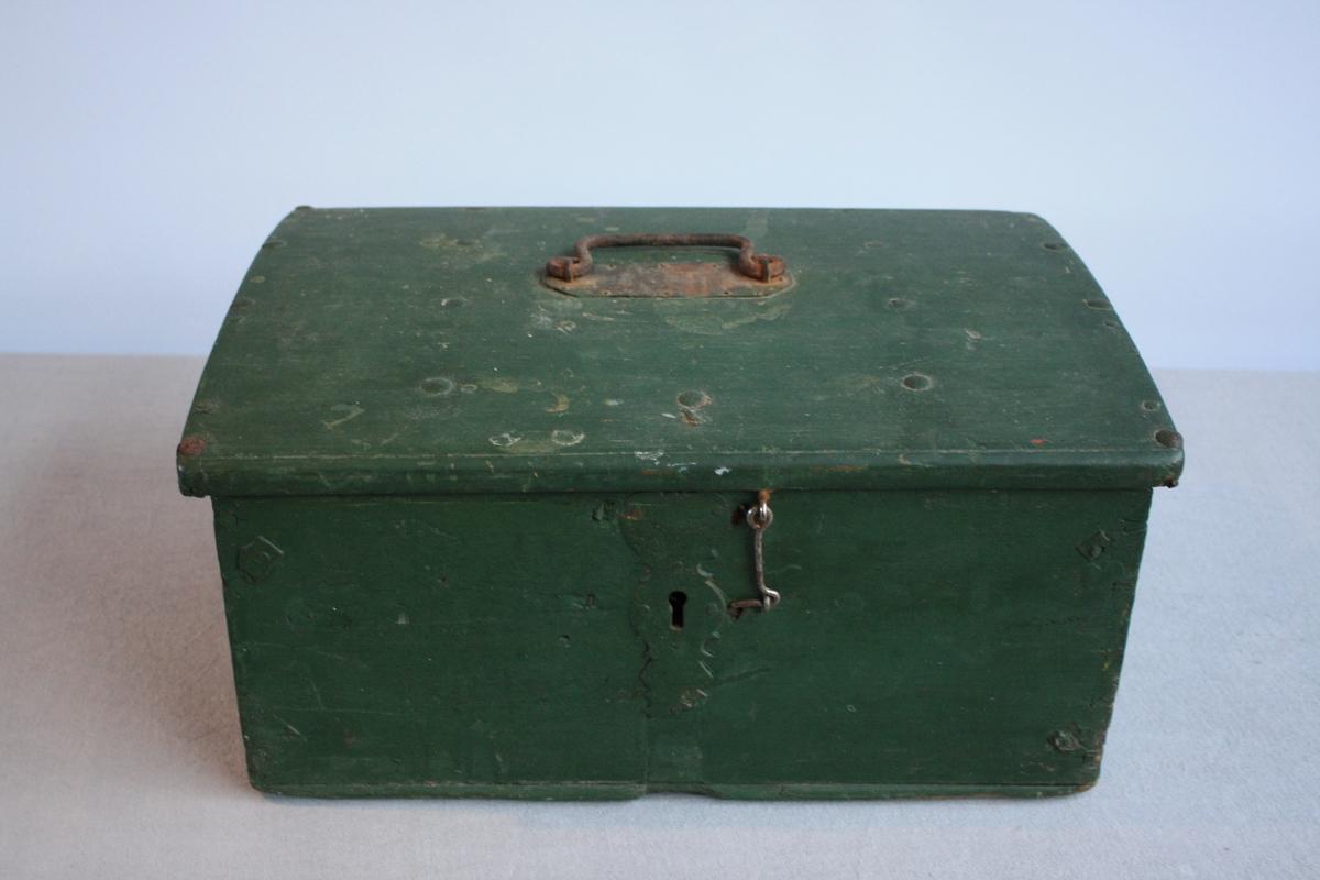 Gønmalt kiste med metall hank på lok. Loket er svakt bua. Innsida på kista er målt rosa. Den opprinnelige låse er ikkje lenger i bruk. Det er i staden satt på ein hasp. Delar av metallbeslag/låsbeslaget er brote av, tydlegvis før kista vart målt grøn.