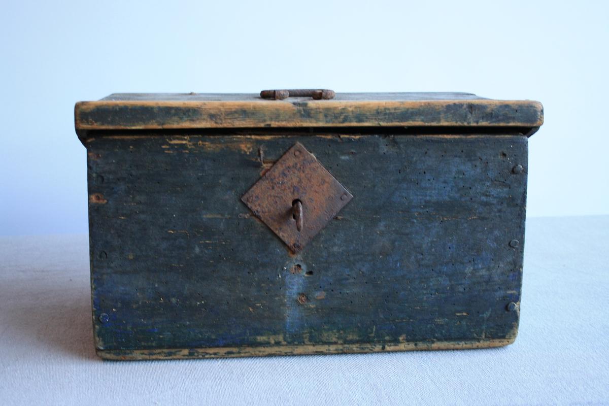 Svartmålt kiste med flatt lok. Metallhank på lok. Kista er set saman av trenaglar. Nøkkel står i lås.