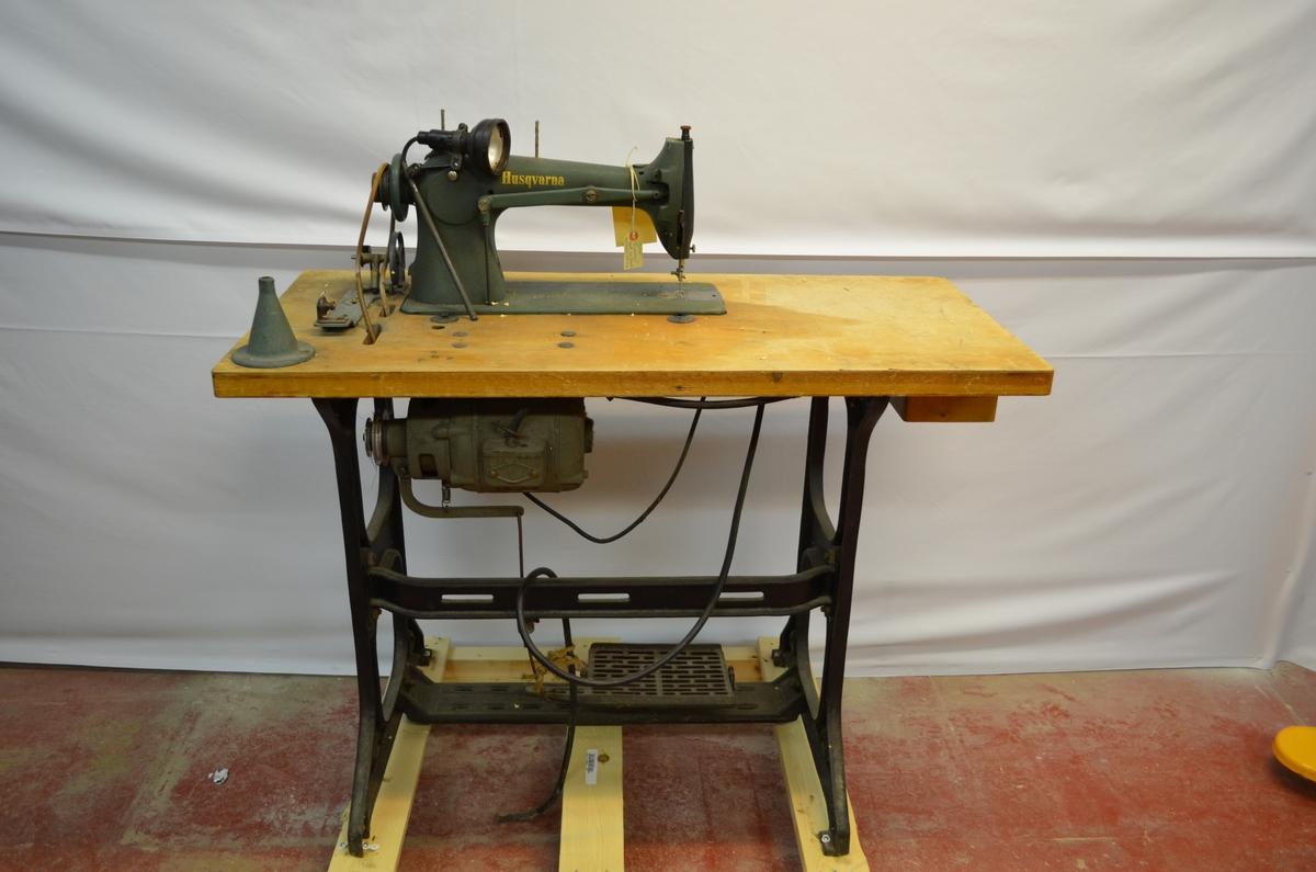 Symaskin fastmontert på bord. Har ei skuff i bordet. Symaskina er modell Husqvarna. Det er ei lampe på bordet - truleg montert i ettertid sidan den er modell Singer. Den er også modernisert med motor som drive drivreima.