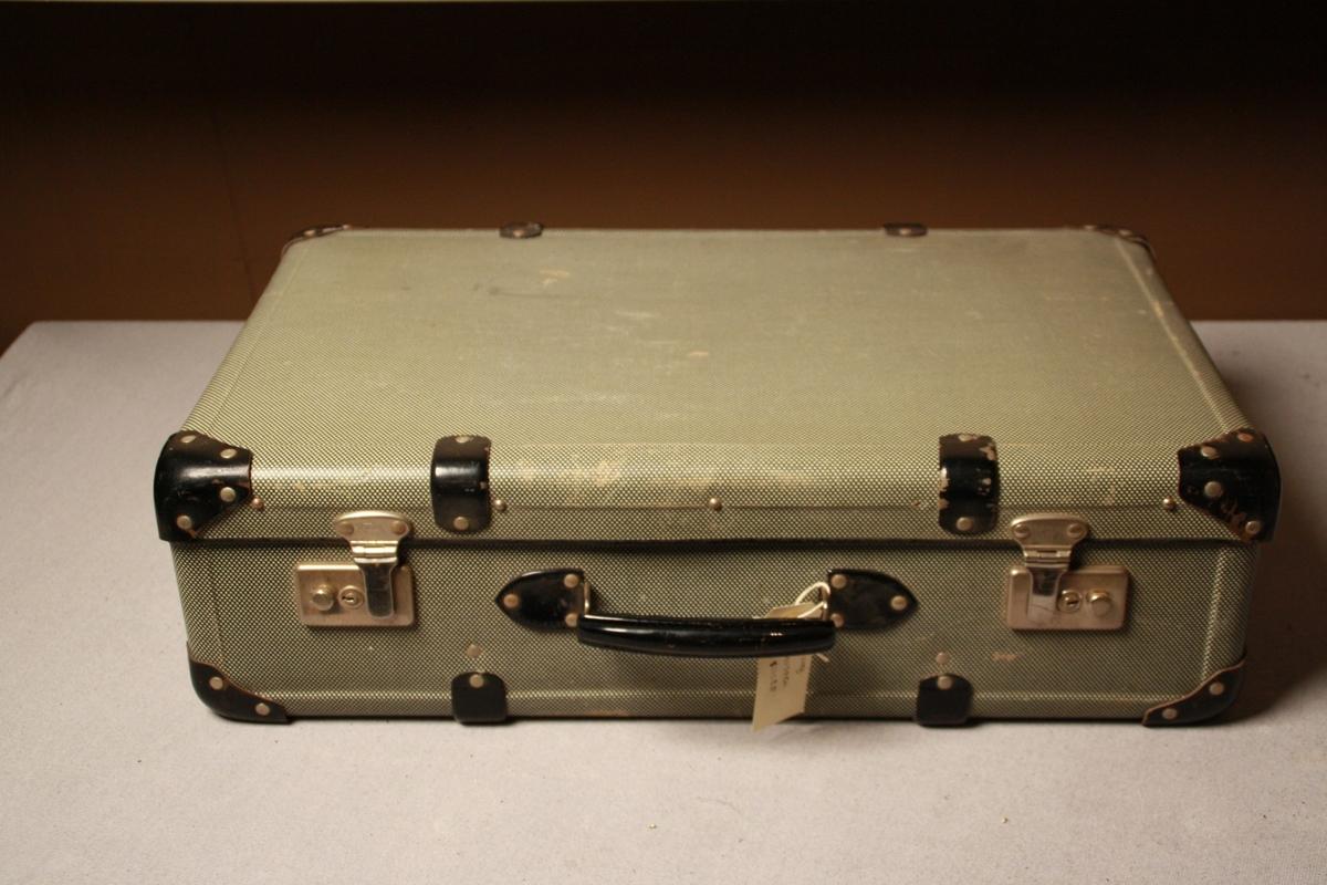 Koffert i papp, grå med kvite prikkar utvendig, beigemønstret inni. Svarte metallforsterkingar i hjørner og kantar, svart handtak. Metallås med Viking rissa inn