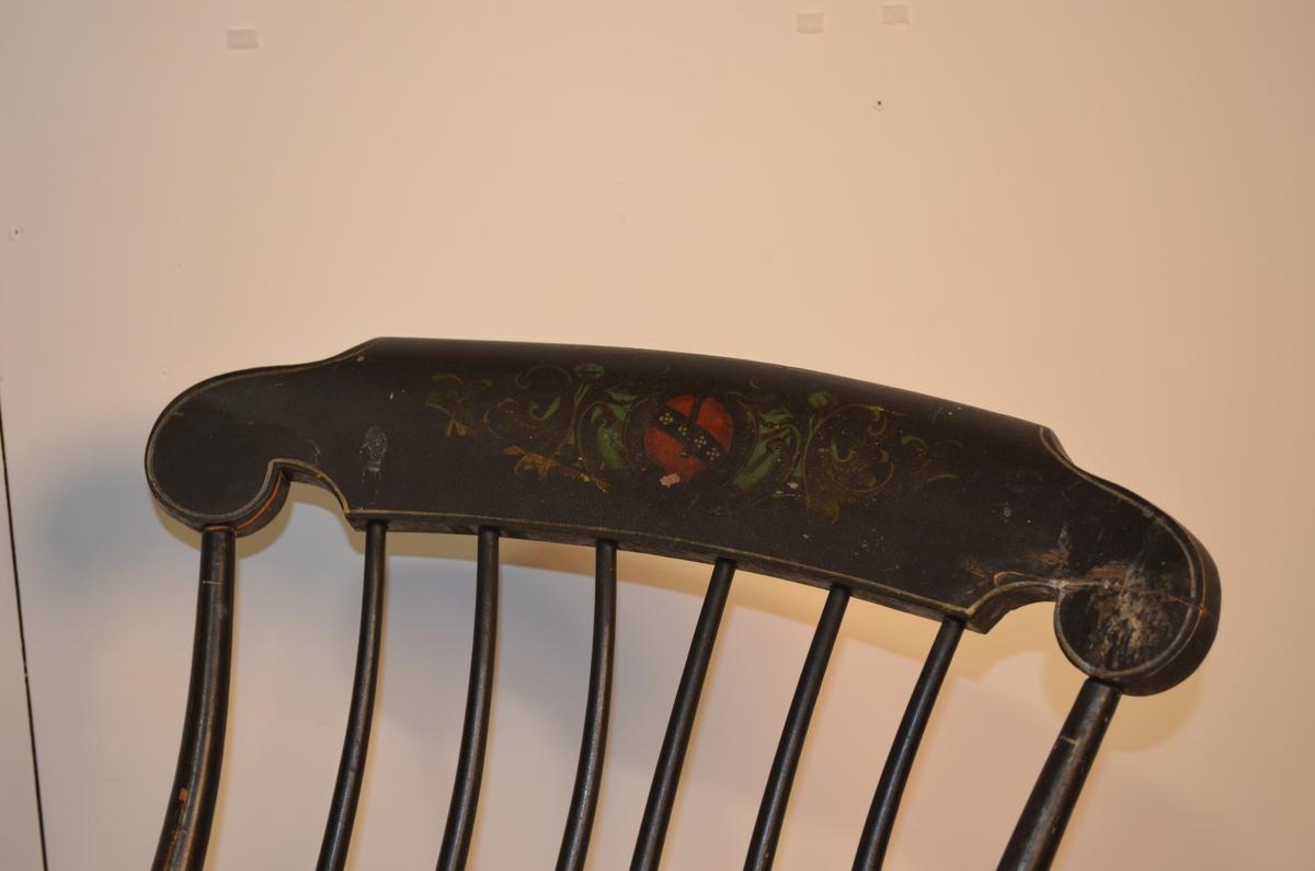 Svartmåla gyngestol med dreide bein. Den har seks dreide ryggspiler og avrunda armlener. Dekorasjon øvst i ryggen og på setet.