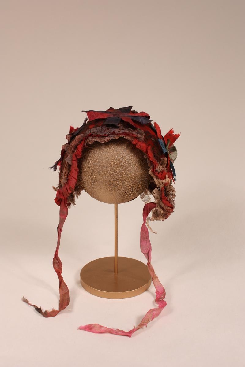 Form: Tre-stykkshue med heilt framstykke og runda bakstykke innfellt. I ull (klede) trekt med svart tyll (flor). To lag med tyll (har vore kvitt el. rosa) og eitt band med rosa silke er foldelagt rundt ansiktet. Silkebandrossettar bak og på sidene.