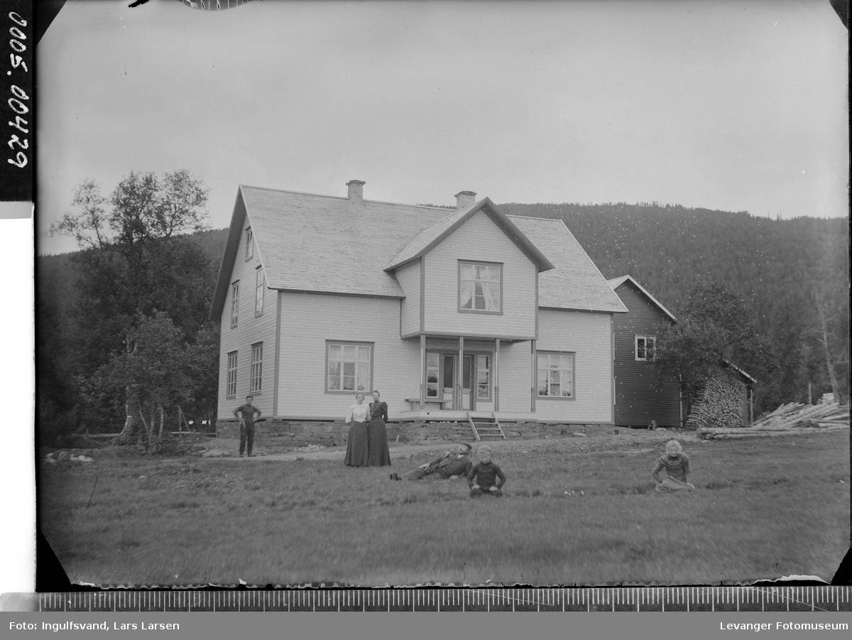 Oversiktsbilde av et bolighus med noen mennesker i forgrunnen.