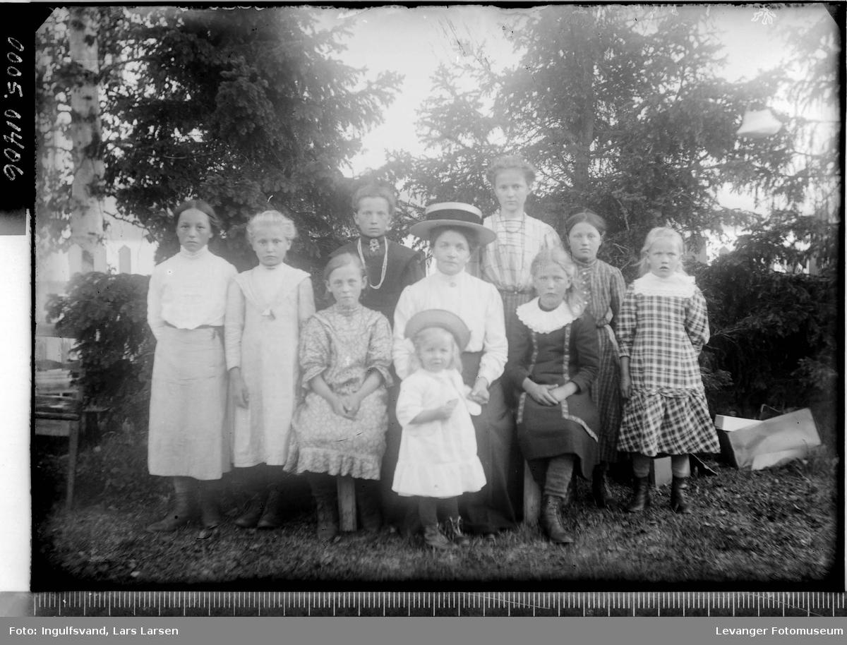 Gruppebilde av en kvinne og ni barn.