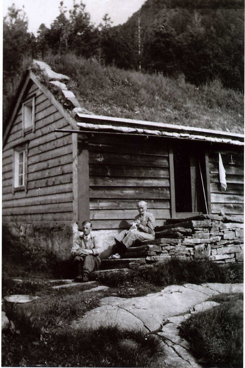 Biletet er tatt på trappa framfor husmannsstova i Movika. An(n)e som budde der kom frå Åsen på Jølster og budde i denne stova frå kr. hundreårskiftet og fram til ho døydde kring 1940. Huset vert også kalla Anestova.