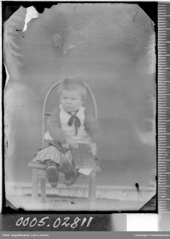 Portrett av et lite barn på en stol.