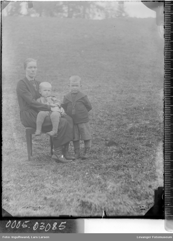 Gruppebilde av en sittende kvinne med to barn.