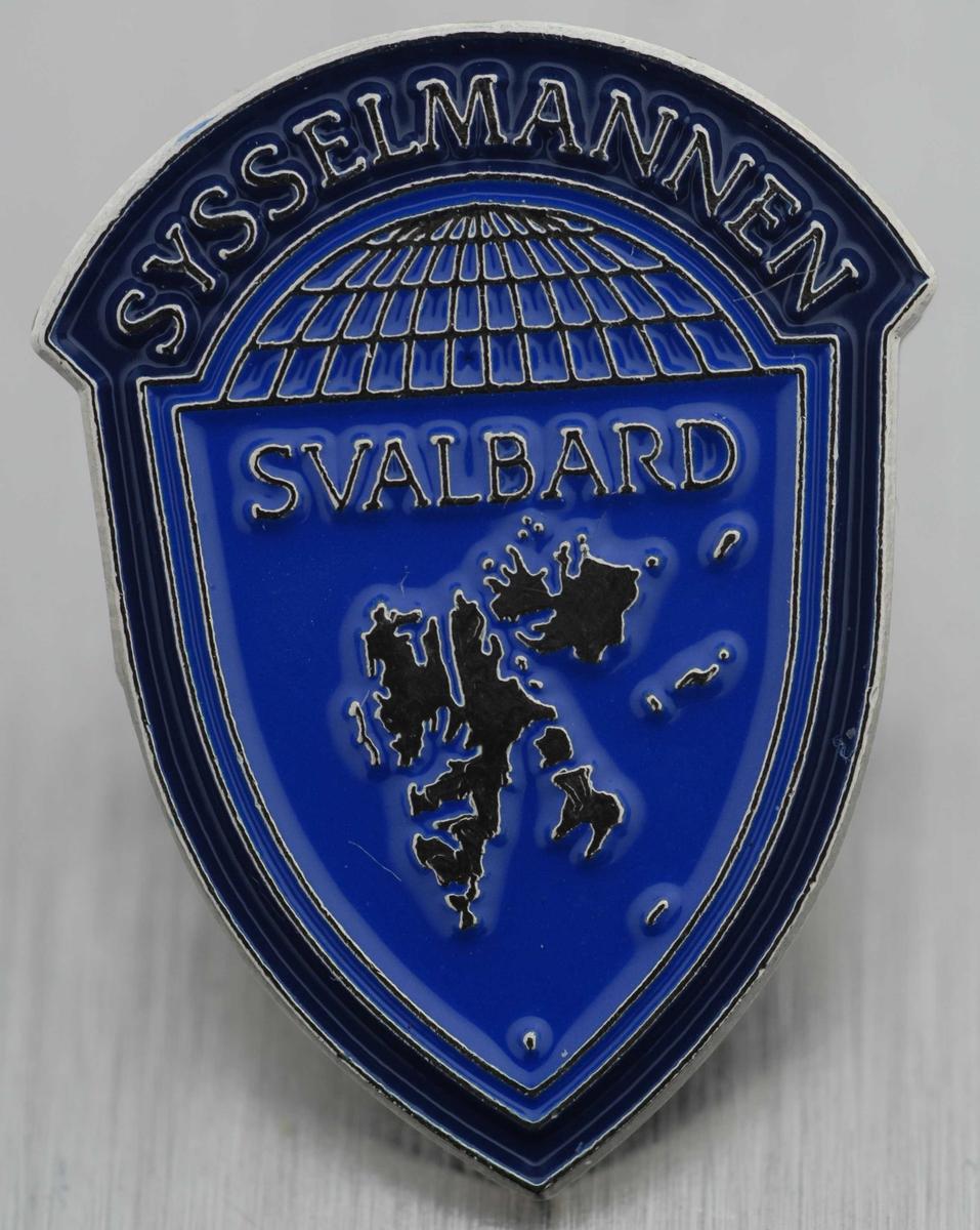 Emaljert pin med Sysselmannens logo i fargene blått og sølv. Formet som et skjold med den nordlige halvkule på toppen med teksten 'Sysselmannen' over, kartet av Svalbard under.