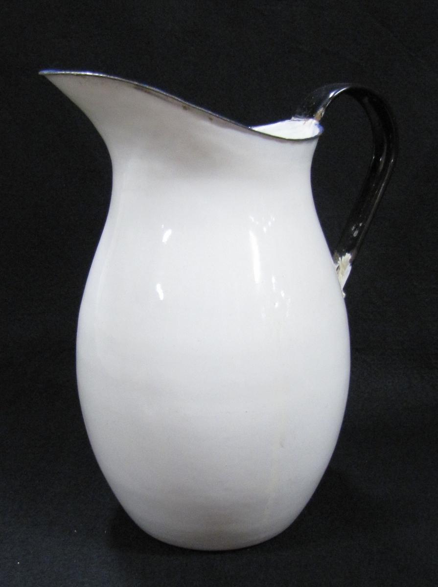 Emaljerad kanna i vitt med blå rand samt svart handtag.  Köpt på auktion hos Knutsson.  Inventering av magasin på Kronogatan.