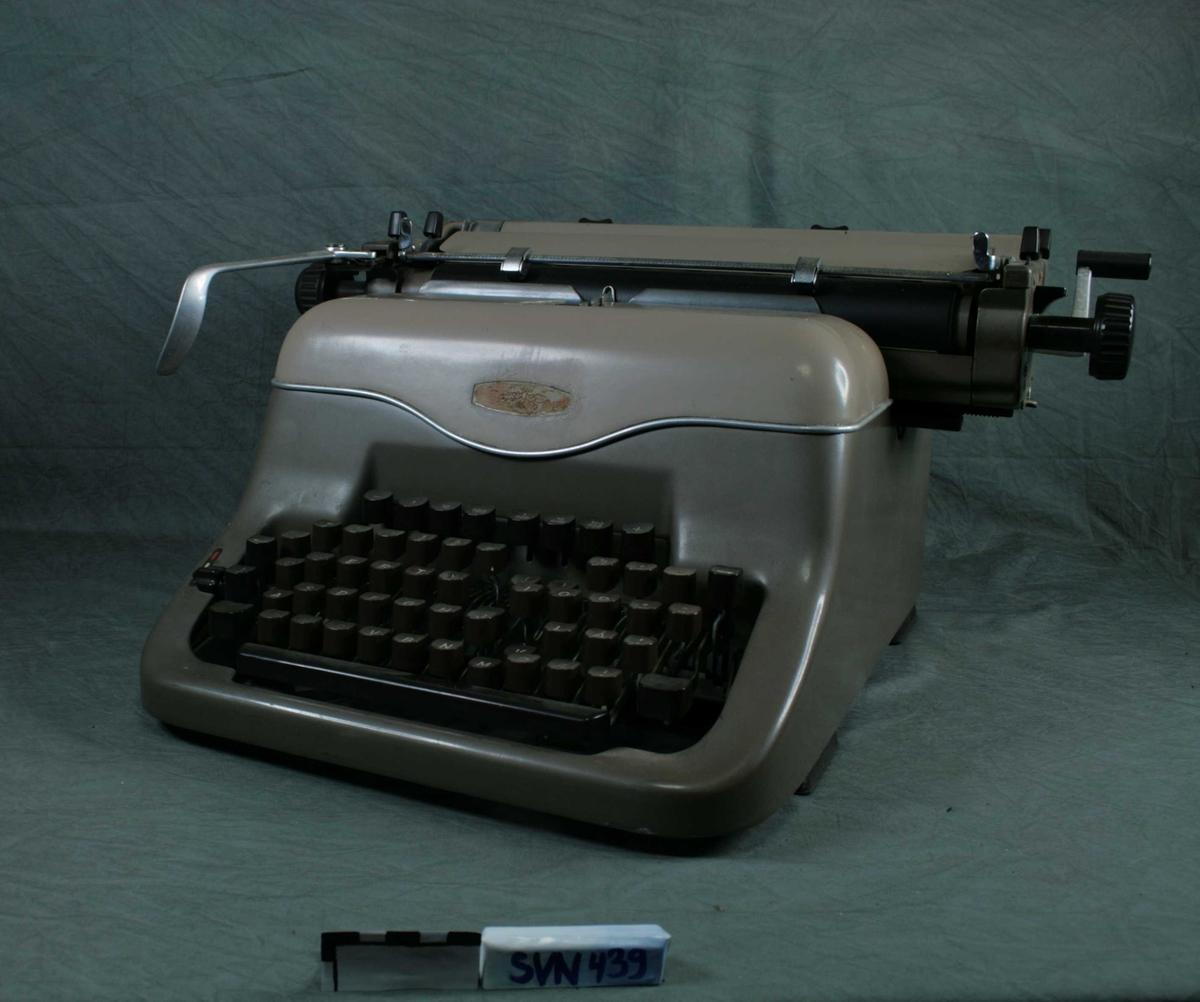 Skrivemaskin i kledt i brunlakkert metall. Brune taster sitter i fem rader på fremsiden. Skrivemaskinen er manuell, og uten strøm.