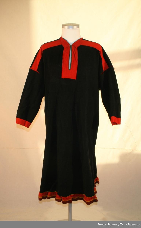 Damekofte i svart ullklede. Holbi i hjemmevevd ull med fargetråd i svart og rødt i tilegg til rødt ullklede og gult klede. Grønt ullklede i foret ved halsen.