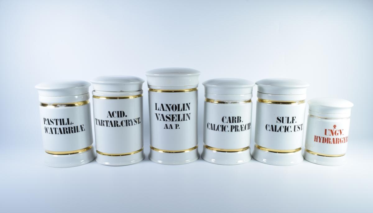 Seks sylindriske porselenskrukker med flatt lokk. Samtlige er dekorert med gullborder øverst og nederst og har skrift i svart eller rødt.