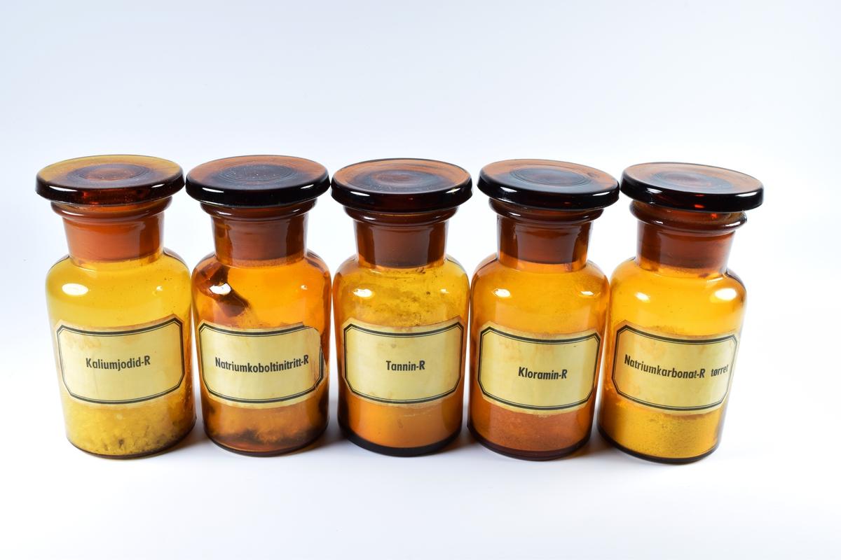 Fem sylindriske flasker i brunt glass med tykk hals og flatt, rundt lokk. Alle flaskene har innhold.