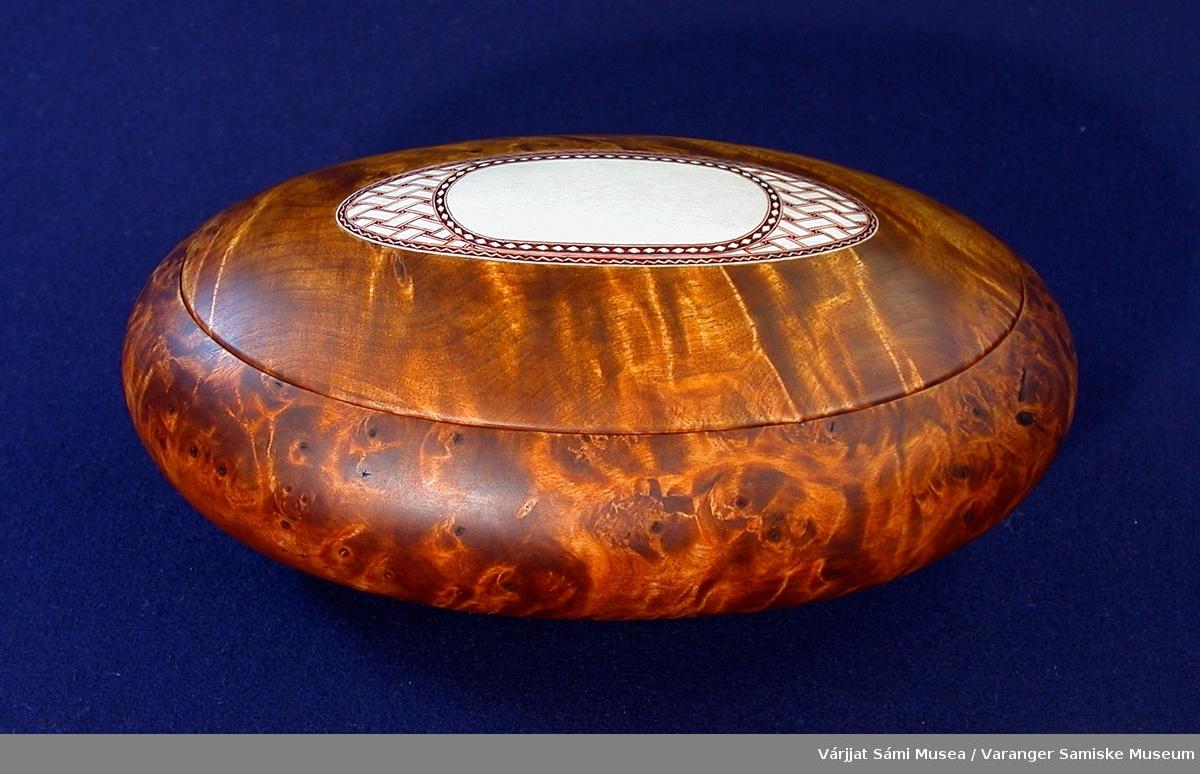 Skrin av bjørk med innfelt horndekor. Dekoren er innfelt i lokket, et ovalt stykke horn som er inngravert og smurt med et fargestoff, formodentlig en blanding av ospebark og et fettstoff.
