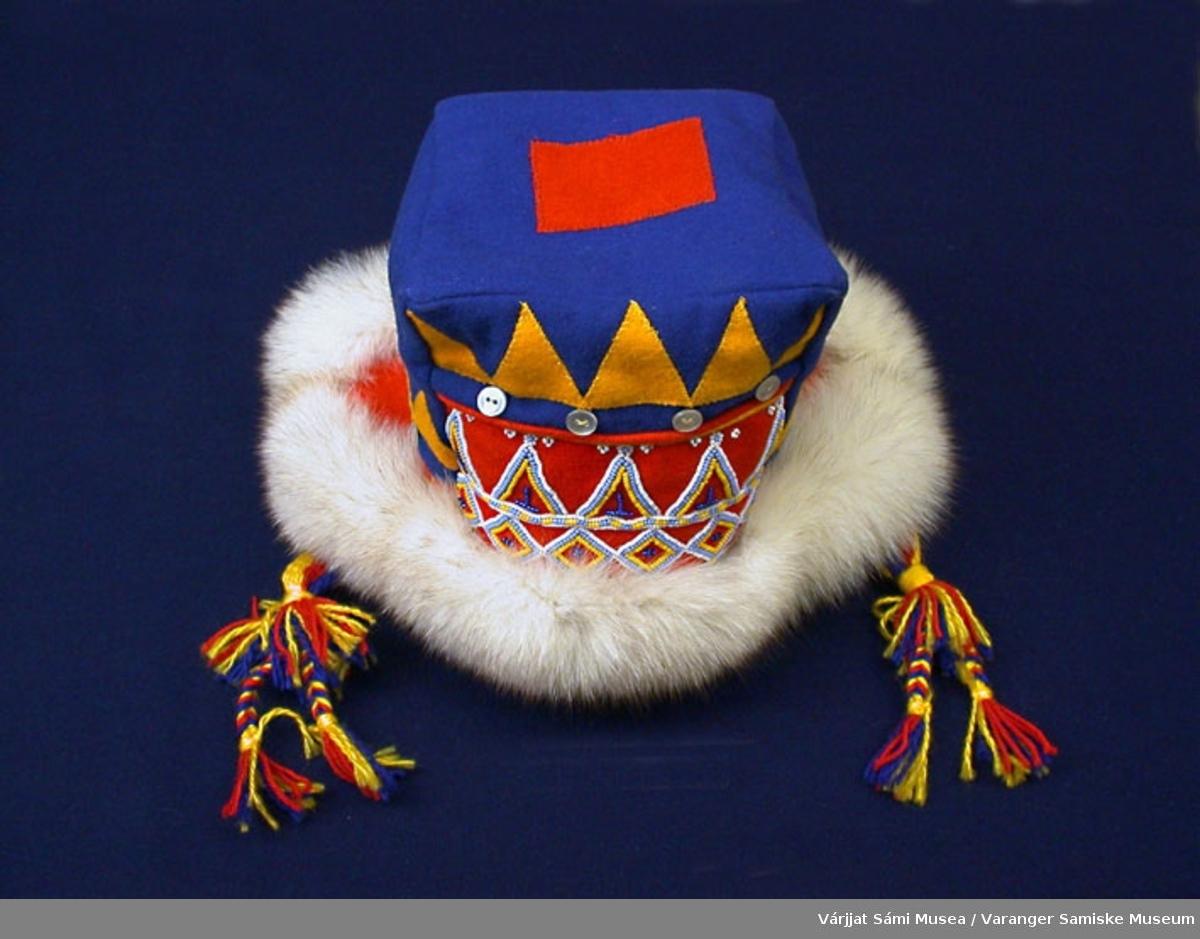 Herrelue av klede, pels og perler. Sydd i blått klede, på toppen av lua et firkantet rødt stykke klede. Pyntet med perler og knapper, sikk sakk gult klede. Snorer av ullgarn i fargene gult, rødt og blått.