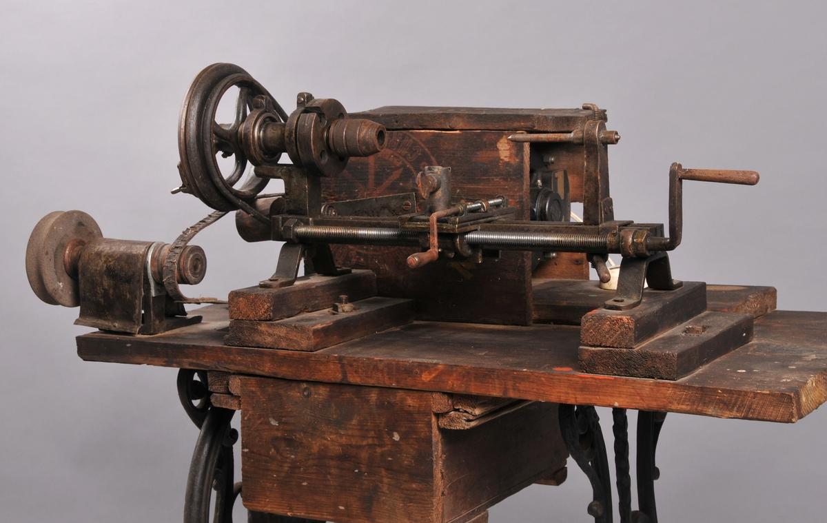 Dreiebenk og slipeskive for metall, drifta elektrisk. Er montera på underdelen til ei symaskin med treplate som dreieutstyret og motor er fest til. Drivreimar av lær. Skuff under arbeidsbrnken.