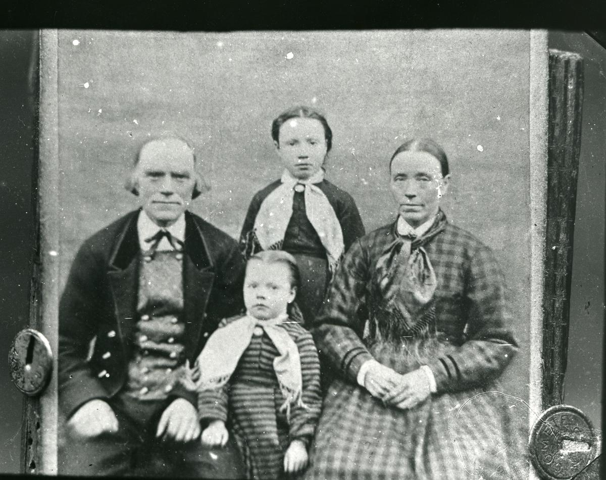 Fotografi av familiefoto festet på treplate med tegnestifter. Kvinne, mann og to barn