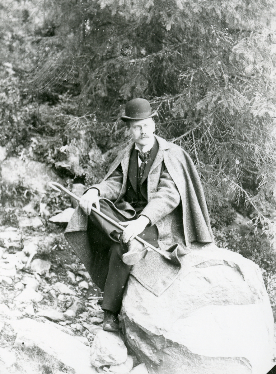 Mann med hatt, sittende på stein i skog