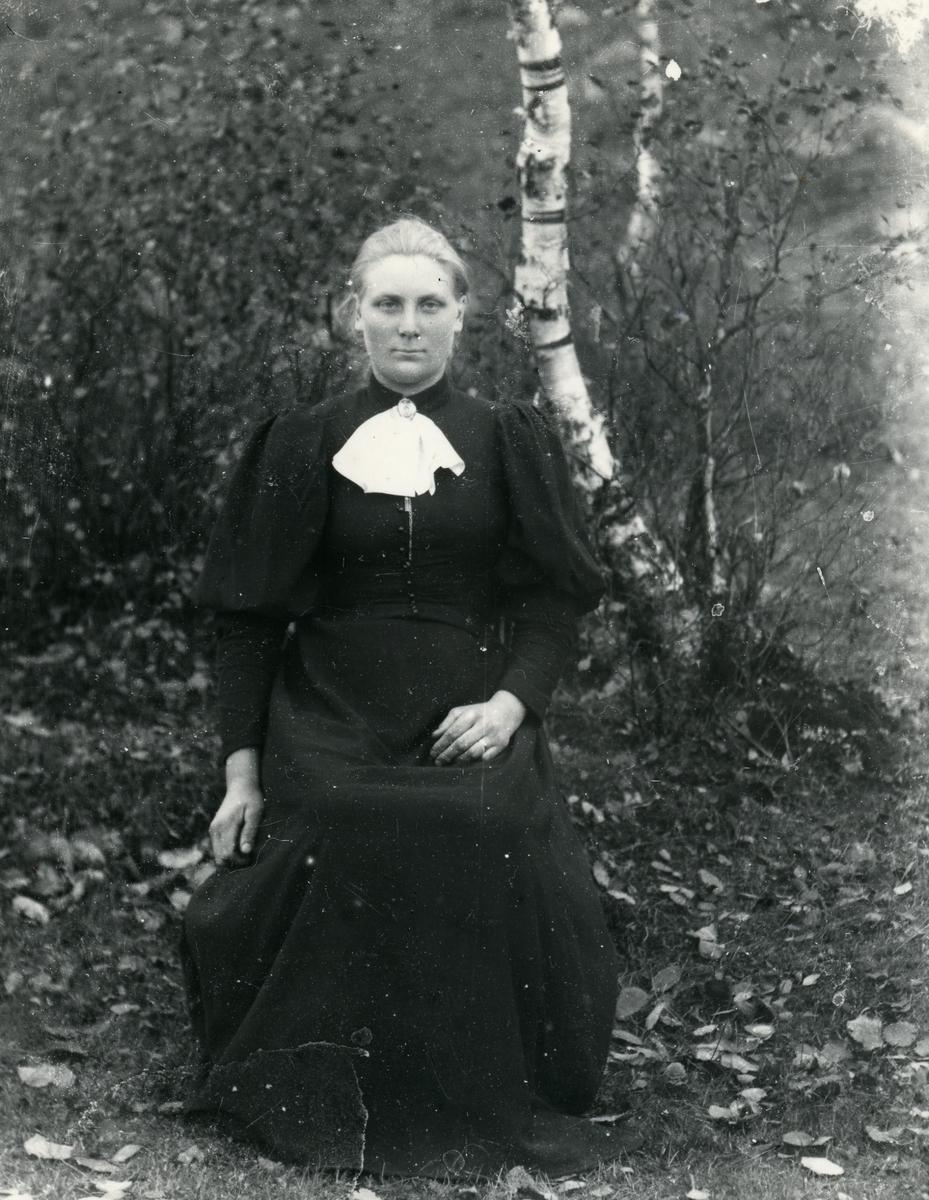 Kvinne fotografert med lerretbakgrunn, halvfigur