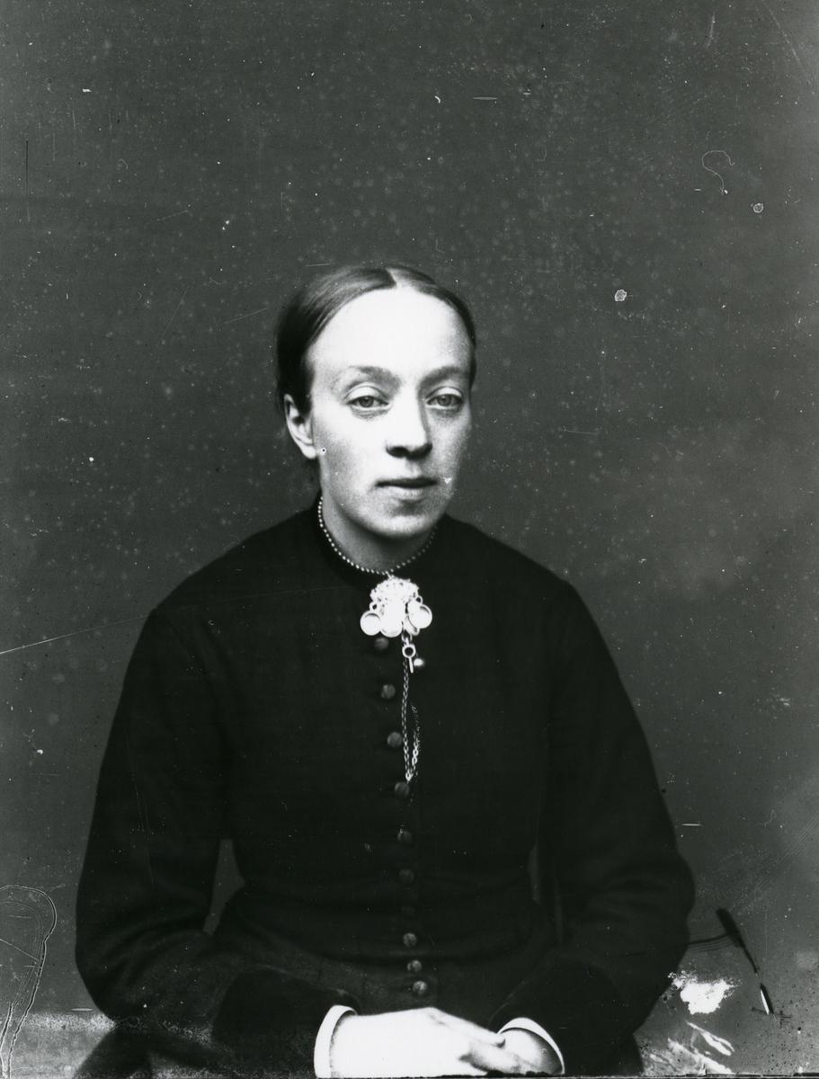 Kvinne i halvfigur, lerretbakgrunn