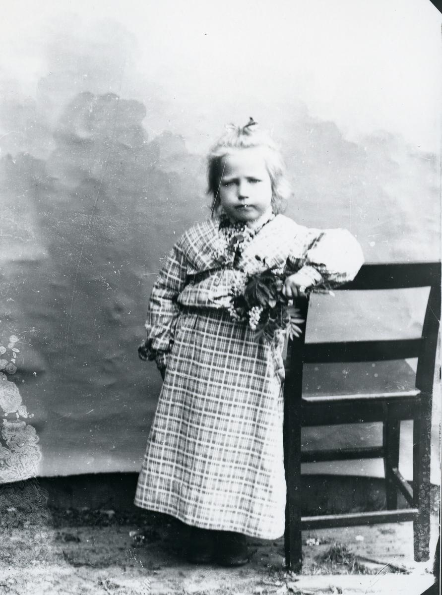 Jente i rutete kjole, med blomsterbukett, stående ved stol