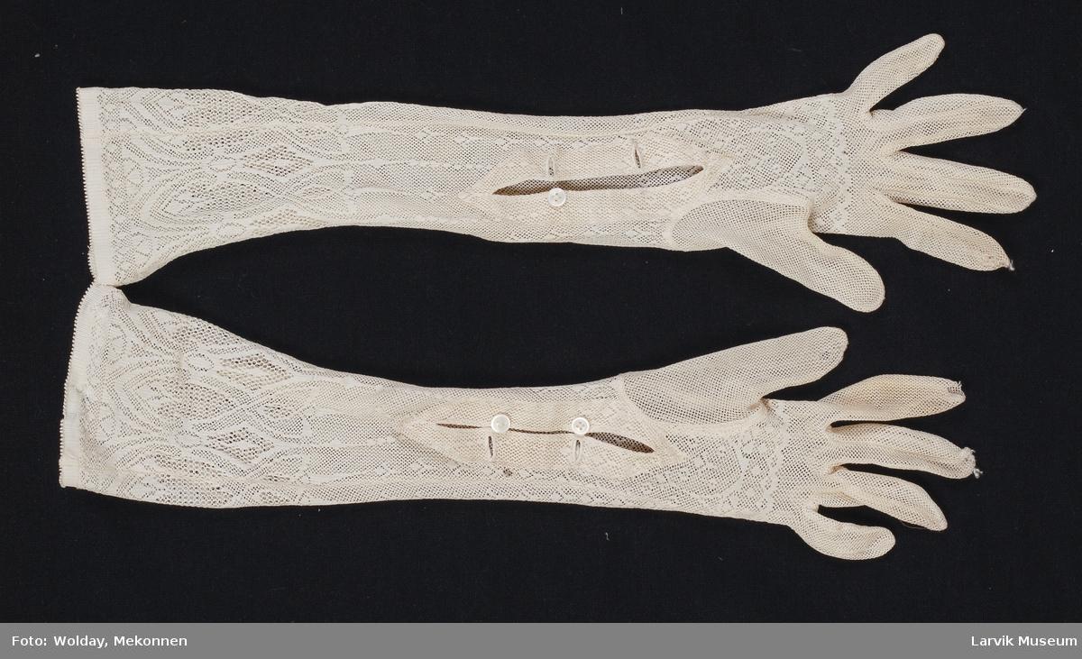 Form: Lange til albuen, to knapper ved håndleddet. Tynne, hullmønsterstrikkede finhansker.