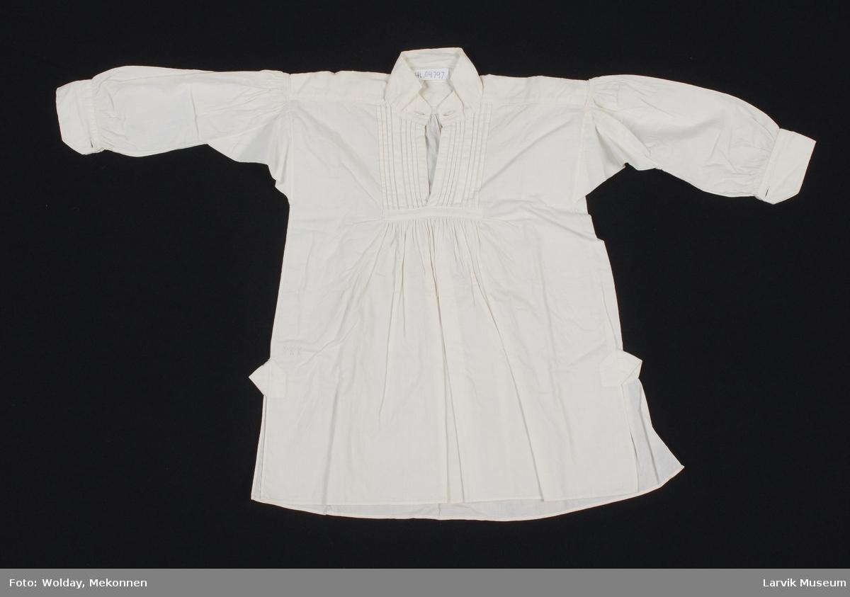"""Form: Liten barneskjorte, med """"kina"""" krage med to """"knappehull"""", vertikale legg på brystet, rynker under legg. Ermer lange, med rynker på skuldrene. Spesielt fint sydd, med MI brodert inn ned til venstre, der en trekant stikker ut."""