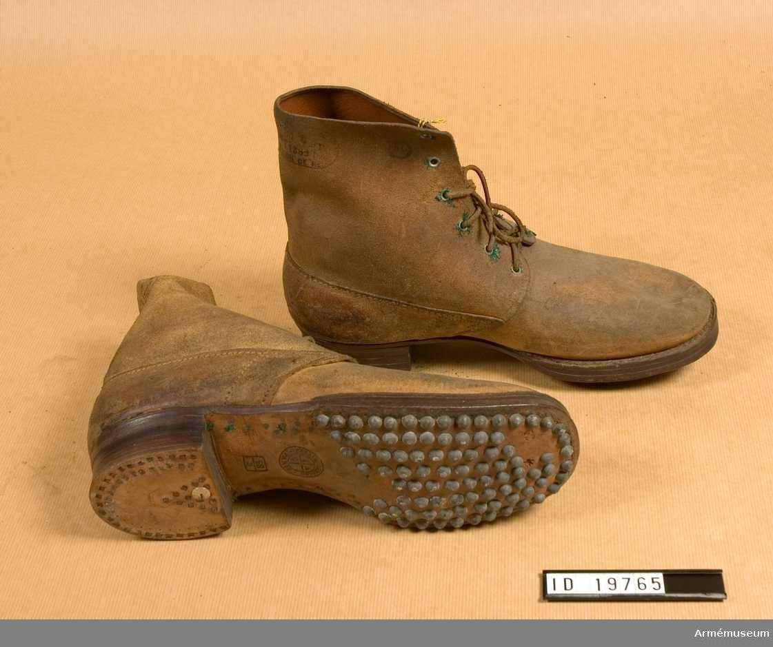 """Grupp C I. Snörskor av grovt brunt läder med inskärning på framsidan. De är försedda med sex par järnringar för att snöra skorna med lädersnören. Sulor och klackar betäckta med järnspikar. På sulorna finns ingraverad stämpel: """"Alex Gendron Paris 3.29"""". En annan stämpel 23/5. På skorna finns stämpel med  påskriften """"1.8.1899"""" """"Commission de reception"""" - uppdrag emottagande. Det finns ytterligare två små stämplar som är oläsliga. Enligt kapten W. Granberg."""