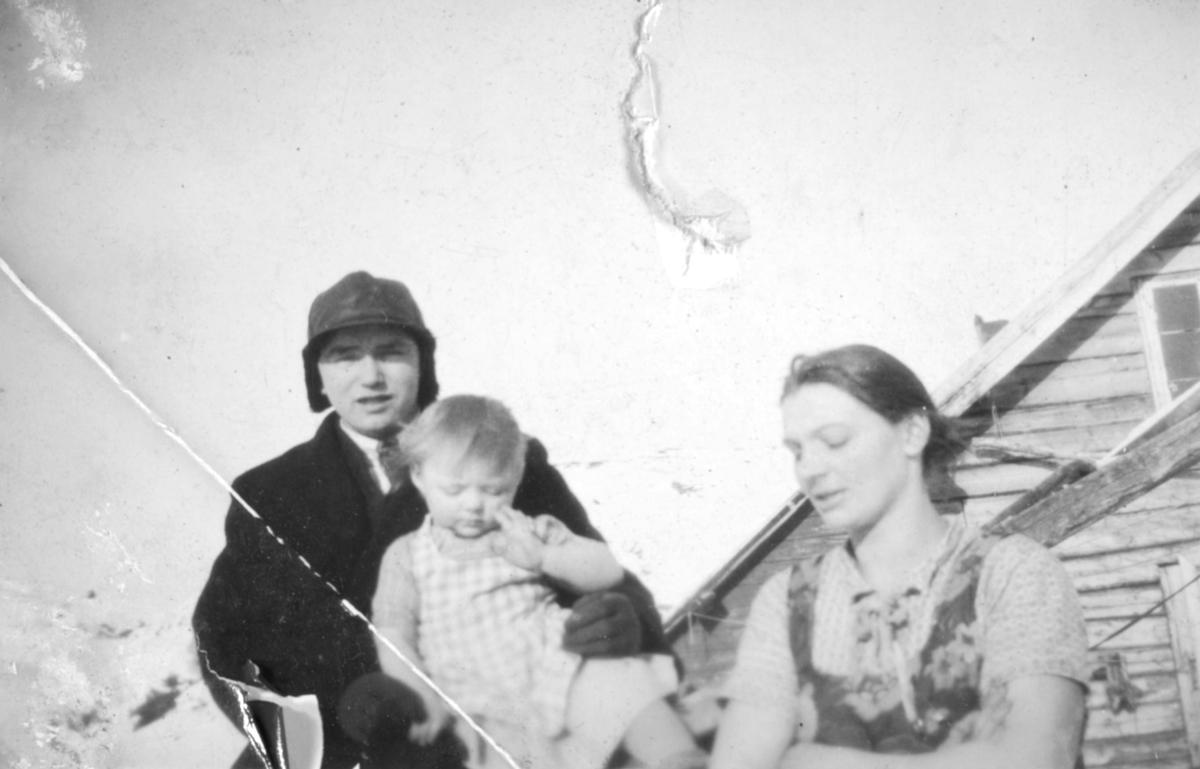 Tre personer, muligens en liten familie med mor, far og barn, fotografert utenfor et hus. Sted og personer er ukjent, men bildet kan være tatt i Kvalsund kommune.