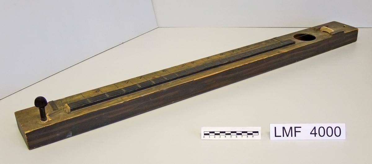 Strengeinstrument som består av en klangkasse med bare én streng. Brukt på Hetland skole (1837), Vanse, Lista.  Form:  rektangulær