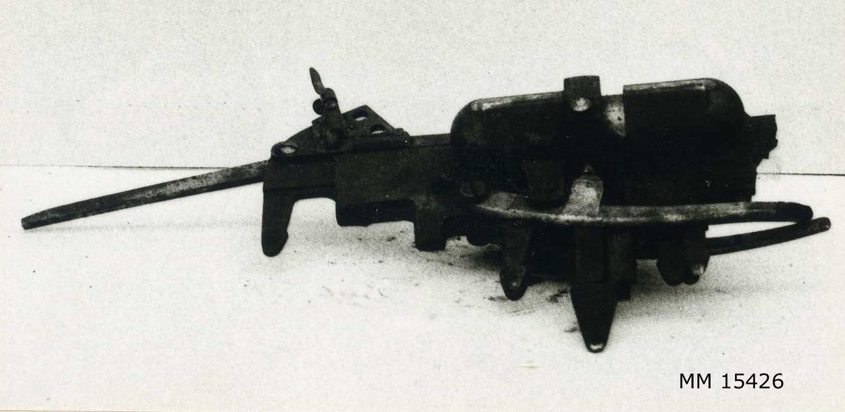 Utlösningsmekanism av stål för nätsax. Utlösningsapparatens huvuddel består av en fjäder som ligger inkapslad i en avlång cylinder på ena sidan av utlösaren. Från denna cylinder utgår två armar till en ståltunga vilken påverkar nätsaxen. På utlösarens ovansida sitter justerskruven. Utlösarens färg: Svart.
