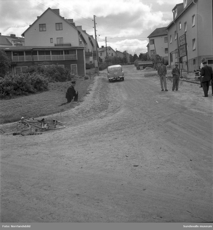 Polis på plats vid Skogsgatan på Östermalm efter en cykelolycka 1949. Det mesta av bebyggelsen är densamma som nu (2015).