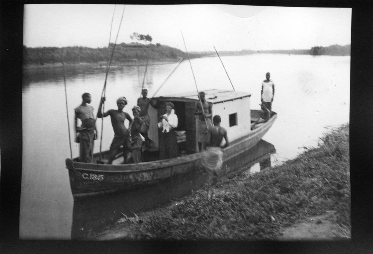 'Diverse fotografier från bl.a. dåvarande Nordrhodesia, nu Zambia, tagna av Konsul Magnus Leijer. ::  :: 8 st män på och invid en mindre båt med däckhus. 4 st av männen håller i pinnar, spjut(?), bland dem är 1 st kvinna stående.'