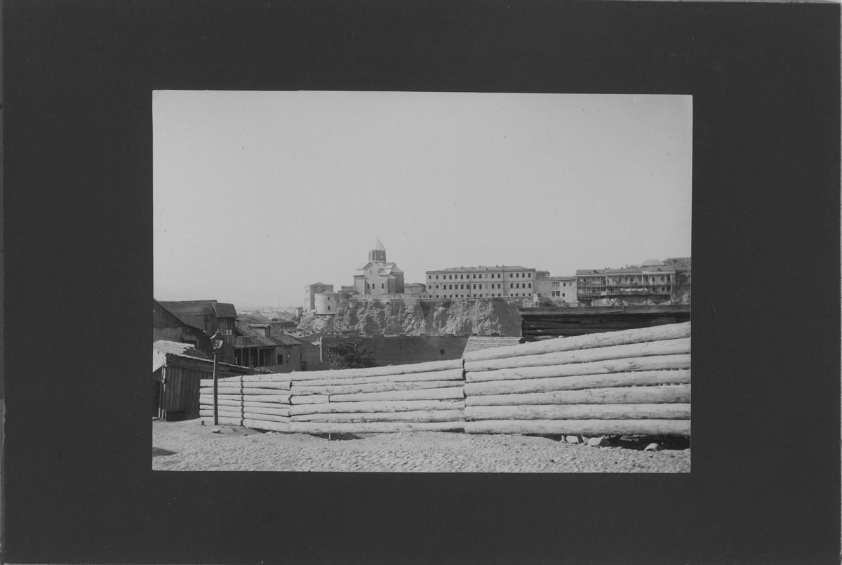 'I förgrunden staket av timmerstockar, innanför hus. På avstånd byggnader på höjd. ::  :: Ingår i serie med fotonr. 5288:1-30. Se även fotonr. 5269-5292 med bilder från Stuxbergs resa till Kaukasien.'