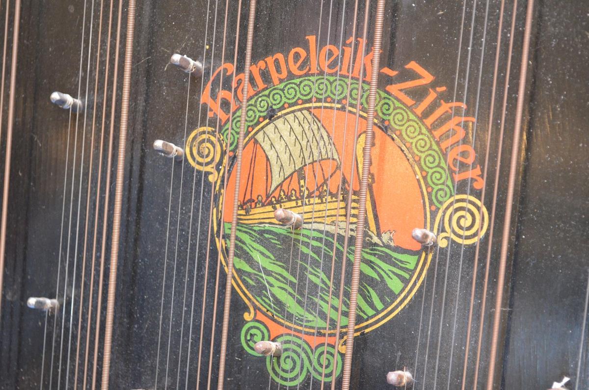 Motiv 1: Vikingskip i sirkel, omrammet av stiliserte akantusranker i fargene gull, grønt og rødt. Navn i tilknytning til motiv 1, harpeleik-zither.   Motiv 2: Lydhull omrammet av grønne bladranker, rødprikkede valmuer og stiliserte akantusranker. Klistrelapp i bunnen av instrumentkassa: Harpeleik-Zither, Trademark. Made in Saxony.  Motiv 3: Notefelt nederst på instrument.