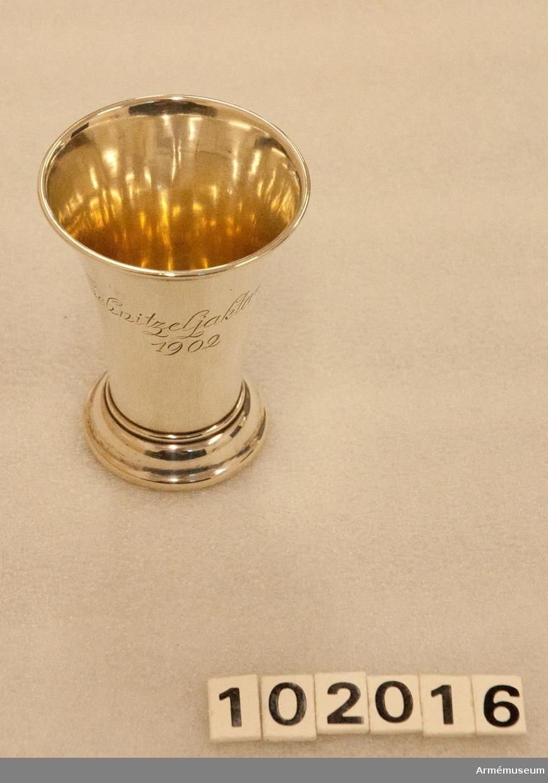 """Silverbägare, Schnitzeljakterna 1902, tillverkad av C G Hallberg, Stockholm, 1902.  Utåt-uppåt vidgad bägare av silver med kantring upptill.  Utkragad fot med s-formig profil. På livet graverad text: """"Schnitzeljakterna 1902"""".   På undersidan silverstämplar: C. G. H., tre kronor, S:t Erik, Z6 (1902)."""