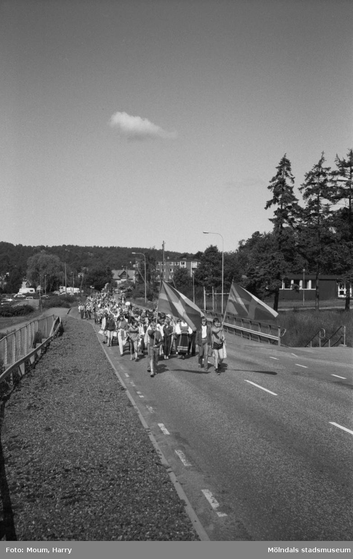 """Nationaldagsfirande i Kållered, år 1983. Festtåg på Streteredsvägen. """"Här kommer vi. Jättekul att marschera tyckte Kållereds skolelever.""""  För mer information om bilden se under tilläggsinformation."""