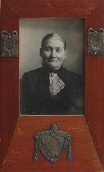 Kvinneportrett. Foto en face, midtskill og glatt hår, sort mønstret kjole med gullbrosje  AAM.11 413 over fichu.