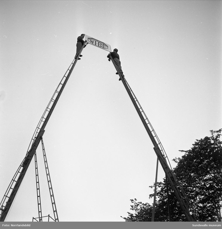 WI-BE-verken (Njurundaverken ?). Monter på Sundsvallsmässan 1954 med massor av höga stegar, samt en parad av vackra damer.