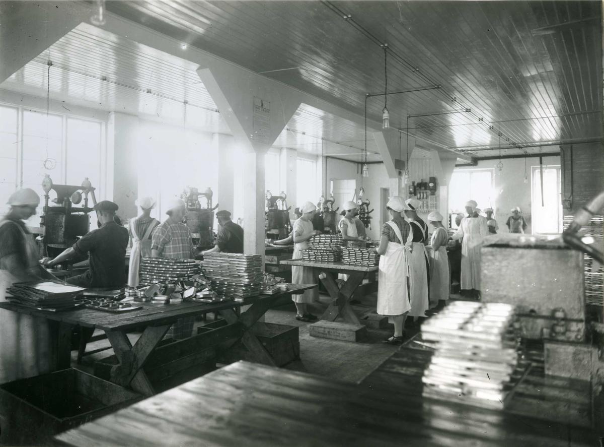 Kvinner i arbeid med hermetikkbokser (sardinbokser?). Mange kvinner står ved flere bord og arbeider. I bakgrunnen sitter fire menn med hver sin maskin.