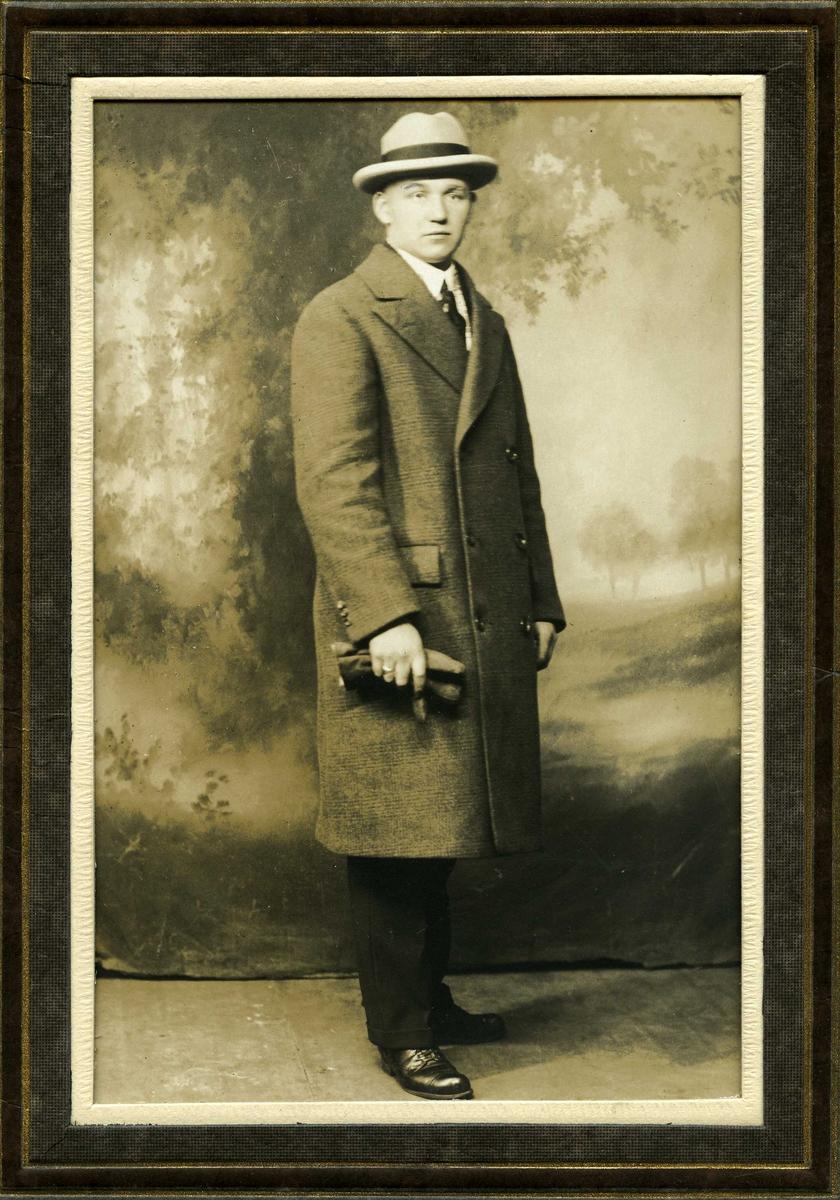 Portrett av stående herre i frakk og med hatt og hansker.