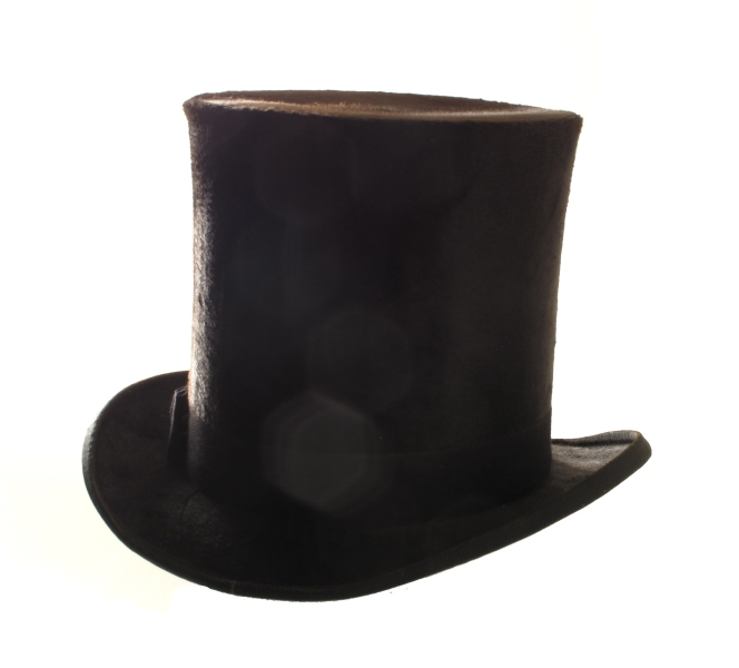 Flosshatt i hatteeske, merket hattemaker P. A. Paulsen, Arendal. a) Flosshatt. Sort floss, purpurfiolett og vinrødt for, trykt med gull midt i bunnen: P. A. Paulsen, Arendal. Svettebrem av konjakkfarget lær. Sort ripsbånd m. sløyfe.    b) Hatteeske. Brunt lær, lærhank med messingbeslag, hvorpå innripet: T. Tellefsen. Foret med gammelrosa fløyel, innv. i bremmen gammelrosa tynt stoff.