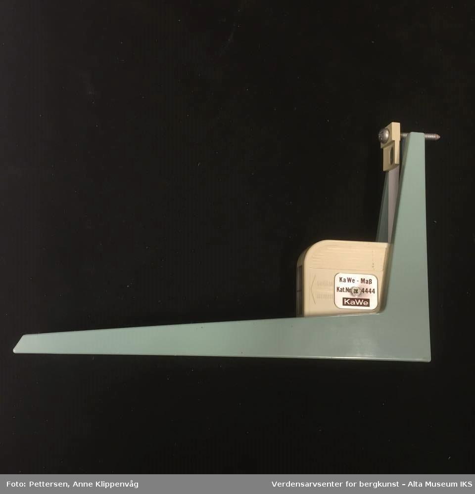 Målebånd i hvitt plastdeksel, montert på en plastvinkel. Målebåndet måler opp til 2 meter. Vinkelen plasseres på gulvet inntil en vegg, og målebåndet rulles helt opp og kan monteres til veggen med en skrue.