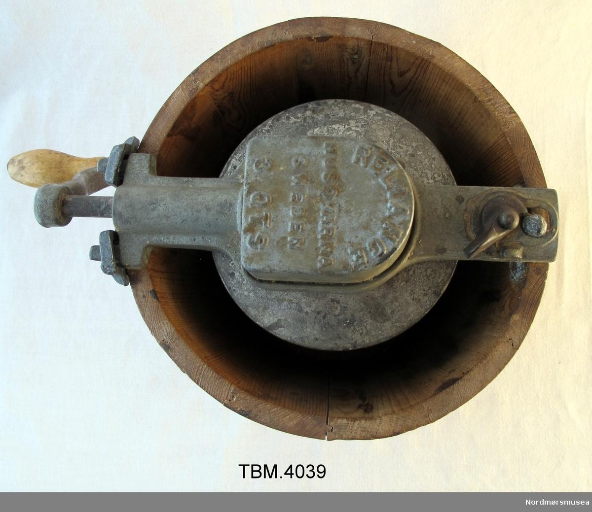 Ein lagga trekopp med ei handriven maskin av metall med sveiv til å piske fløyten til iskrem.
