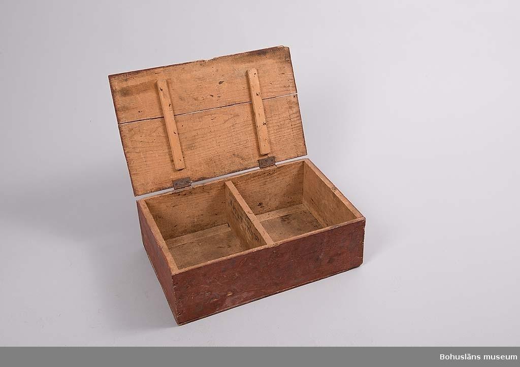 Rektangulär låda med lock. Locket sitter fast med två små gångjärn. Invändigt avdelad i två lika delar. Utvändigt målad i brunrött.  Ingår i redskapsbestånd ur sjöbod från Hällsö, Havstenssund, Tanum sn. Se UM017521.