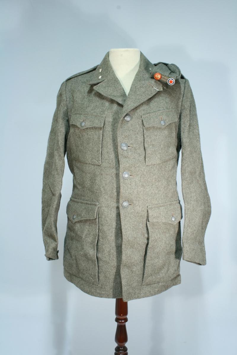 Uniform i grå-grønn farge etter svensk modell. Nedbrettet krage med 2 sølvstjerner, 4 løveknapper i metall, 4 lommer foran med klaffer og løveknapp, 2 innerlommer, skulderklaffer uten distinksjon.   En båtlue med metallrosett. En bukse med strikk.