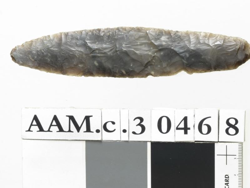 Dolk av mørk grå flint, av typen H. Gjessing: Rogalands Stenalder, fig. 197, men mer jevnbred og mindre tilspisset i begge ender. Et par skall avslått på den ene kanten av grepet,ellers godt bevart og pent hugget.